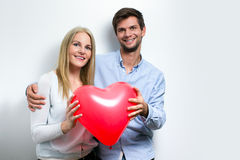 Young couple smiling and holding a heart Stock Image