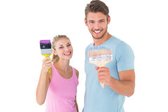 Young couple smiling and holding paintbrushes Royalty Free Stock Photography