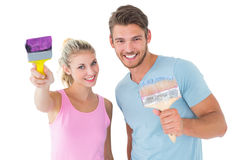Young couple smiling and holding paintbrushes Royalty Free Stock Photos