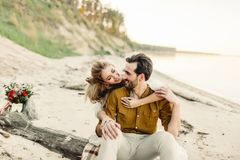 A young couple is smiling and hugging on the beach. Beautiful girl embrace her boyfriend from back. Wedding walk Royalty Free Stock Image
