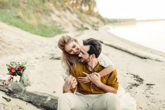 A young couple is smiling and hugging on the beach. Rustic wedding ceremony outdoors. Bride and groom look at each other Royalty Free Stock Photos