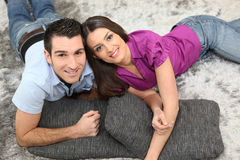 Young couple smiling laid on cushions Royalty Free Stock Photos
