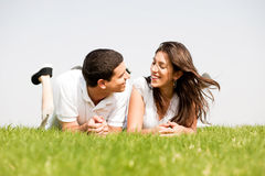 Young couple smiling by laying down. In a green grass field,outdoor Stock Image