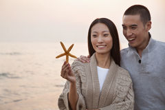 Young Couple Smiling and Looking At a Seashell Royalty Free Stock Photography