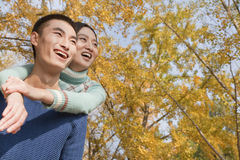 Young couple smiling and piggyback in park in autumn Stock Photography
