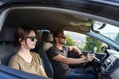 Young couple smiling, sitting in car, enjoying mountains view. Young beautiful couple smiling, sitting in car, enjoying mountains view. Copy space Royalty Free Stock Photos