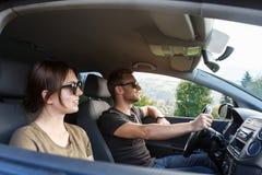Young couple smiling, sitting in car, enjoying mountains view. Young beautiful couple smiling, sitting in car, enjoying mountains view. Copy space Stock Photos