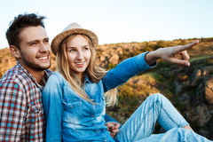 Young couple smiling, sitting on rock in canyon, enjoying view. Stock Photo
