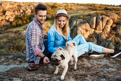 Young couple smiling, sitting on rock in canyon, stroking pug dog. Royalty Free Stock Image