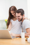 Young couple smiling and using laptop Royalty Free Stock Photo