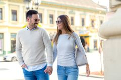Young couple smiling while walking outdoors on sunny d royalty free stock images