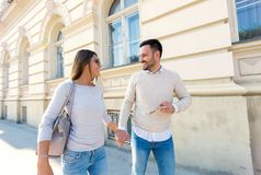 Young couple smiling while walking outdoors on sunny day. Beautiful young couple smiling while walking outdoors on sunny day Stock Images