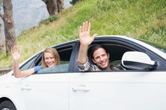 Young couple smiling and waving Royalty Free Stock Images