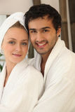 Young couple smiling wearing bathrobe Stock Image