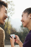 Young couple smiling, woman holding digital camera Stock Image