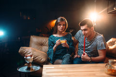 Young couple smoking hookah on leather couch Royalty Free Stock Image