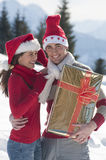 Young couple on the snow with Christmas gift Royalty Free Stock Photography