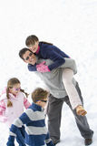 Young couple in snow field by son and daughter (7-9), man carrying woman on back, smiling Stock Photography