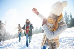 Snowball fight. Young couple in snowball fight royalty free stock photos