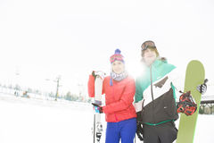 Young couple with snowboard and skis in snow Royalty Free Stock Photo