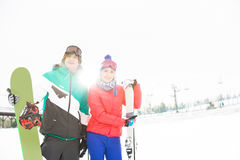 Young couple with snowboard and skis in snow Royalty Free Stock Image