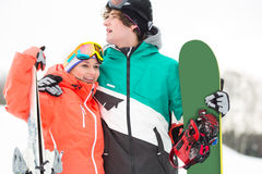 Young couple with snowboard and skis in snow Stock Photo