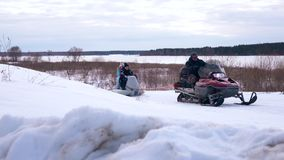 Young couple on snowmobile riding on field stock footage
