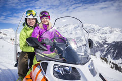 Young couple on a snowmobile ski resort. Men and his girlfriend riding snowmachine sled on their vacation in alps Royalty Free Stock Image