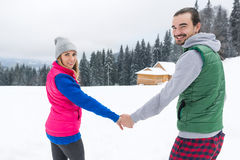 Young Couple Snowy Village Wooden Country House Man And Woman Winter Snow Resort Cottage. Holiday Vacation Royalty Free Stock Images