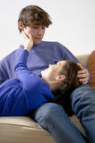 Young couple on the sofa. Caressing each other Stock Photography