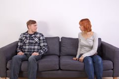 A young couple on a sofa Stock Images