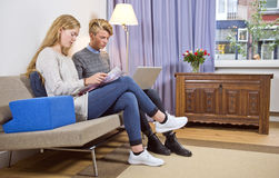 Young couple on sofa doing their personal administration Royalty Free Stock Images