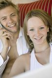 Young couple on sofa man on cell phone portrait Stock Photography
