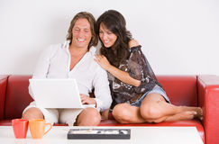 Young couple on the sofa play with the laptop Royalty Free Stock Photography