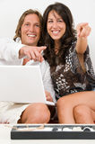 Young couple on the sofa play with the laptop Royalty Free Stock Photo