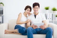 young Couple on sofa with tablet Stock Images