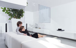 Young couple on sofa watching TV. Rear view of young couple on sofa watching TV in living room Stock Photo