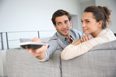 Young couple on sofa watching tv Stock Photos