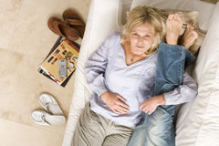 Young couple on sofa, woman embracing man's legs, smiling, portrait, elevated view Royalty Free Stock Image