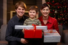 Young couple and son at christmas. Portrait happy young couple and son at christmas, holding presents, smiling Royalty Free Stock Photo