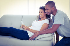 Young couple with sonogram. On sofa at home stock image