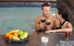 Young couple in spa. Young couple enjoying relaxation in spa with glass of wine Stock Photo