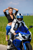 Young couple with a speed motorcycle Stock Photos