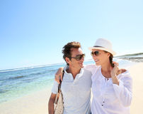 Young couple spending holidays on the beach. Trendy couple walking on a sandy beach Stock Photography