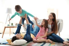 Young couple spending time with children. At home. Happy family stock image
