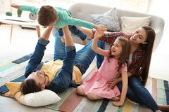 Young couple spending time with children. At home. Happy family royalty free stock image