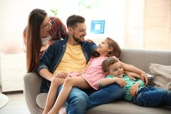 Young couple spending time with children at home. Happy family royalty free stock image
