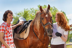 Young couple spending time together with horse Royalty Free Stock Photo