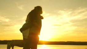 A young couple is spinning in a sunset dance on the beach. Loving man and woman dance in bright rays of sun on the stock footage