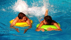 Young couple splashing and having fun in swimming pool on inflatable rings stock video footage